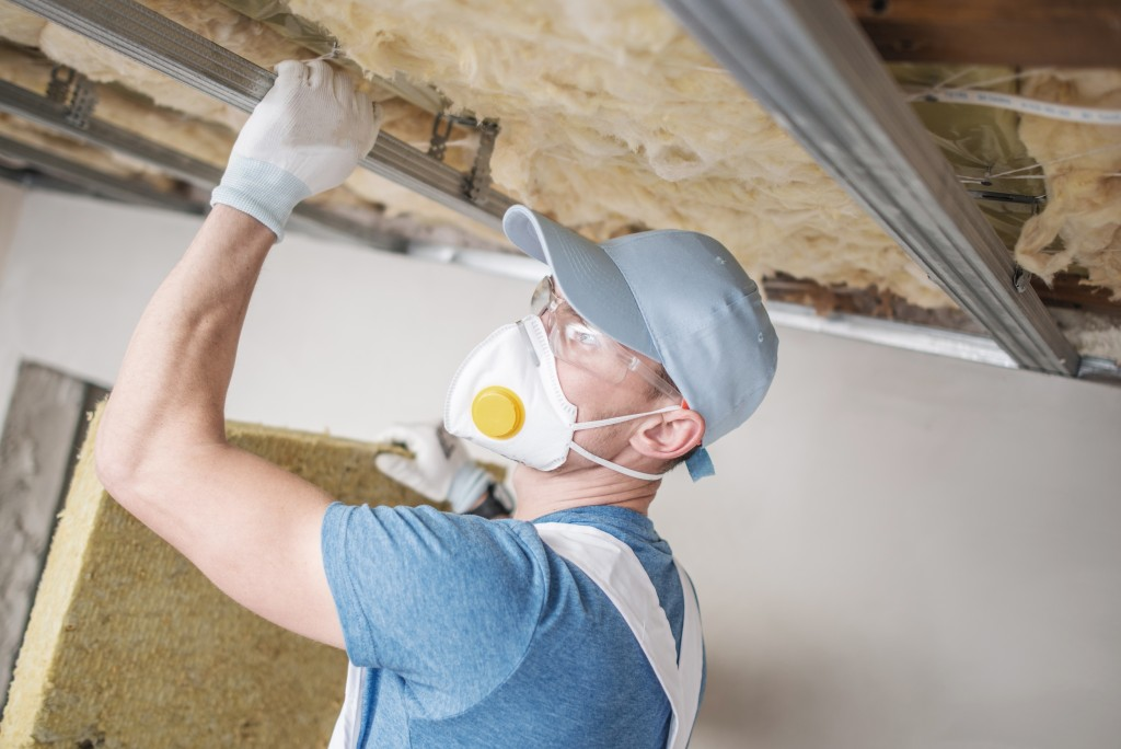 worker insulating house ceiling