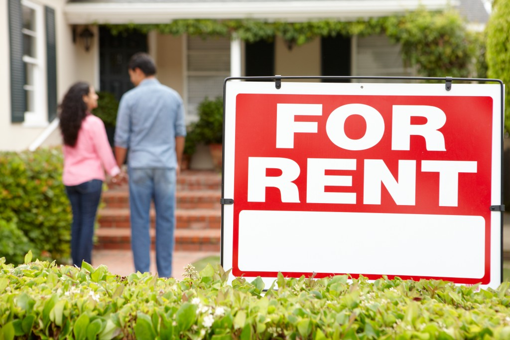 "Couple with ""for rent"" sign"