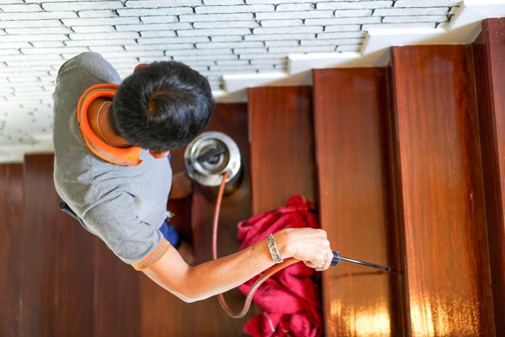 exterminator spraying wooden stairs