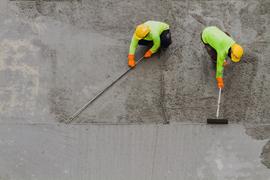 2 concrete workers spreading cement