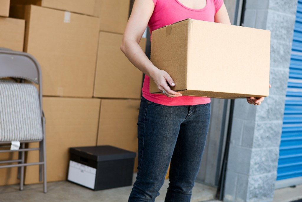 Woman holding box in storage unit