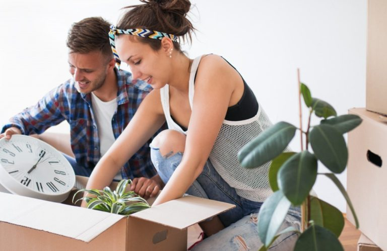 Couple packing their items inside a box