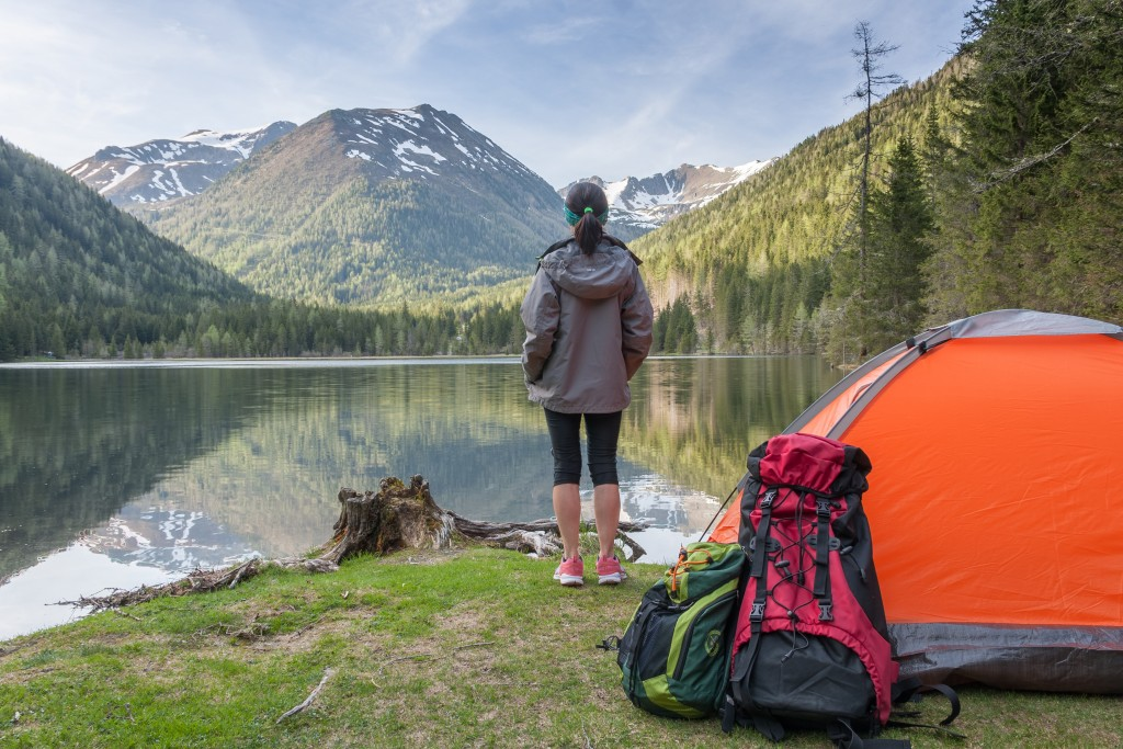 woman camping in a mountain beside the lake