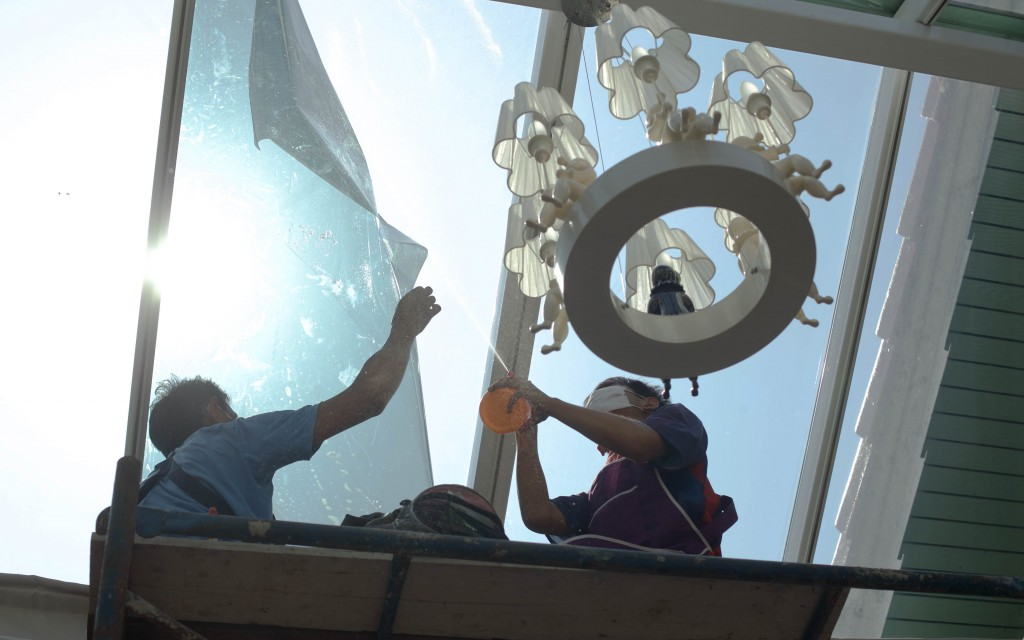 workers putting window tint on conservatory window