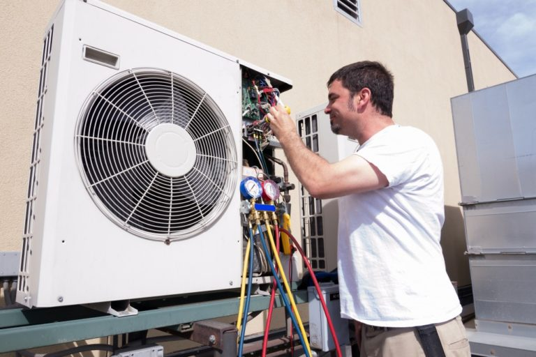 HVAC technician working on condensing unit