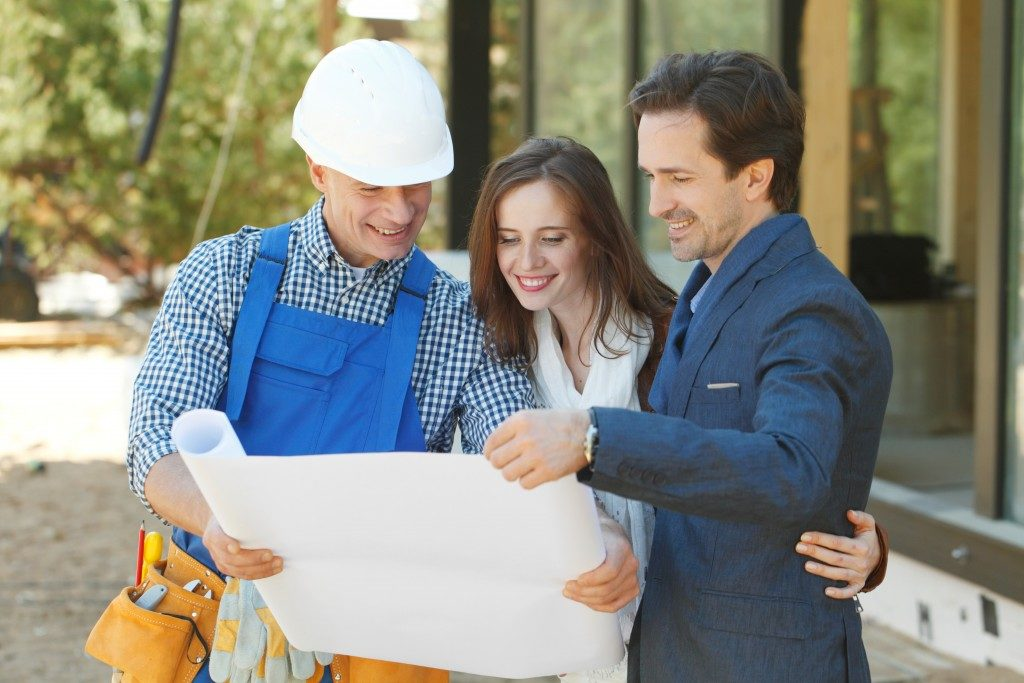 contractor and couple looking at house plan