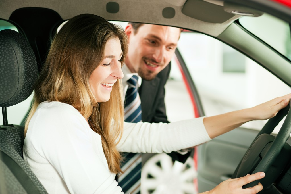 Car salesman showing car features to client