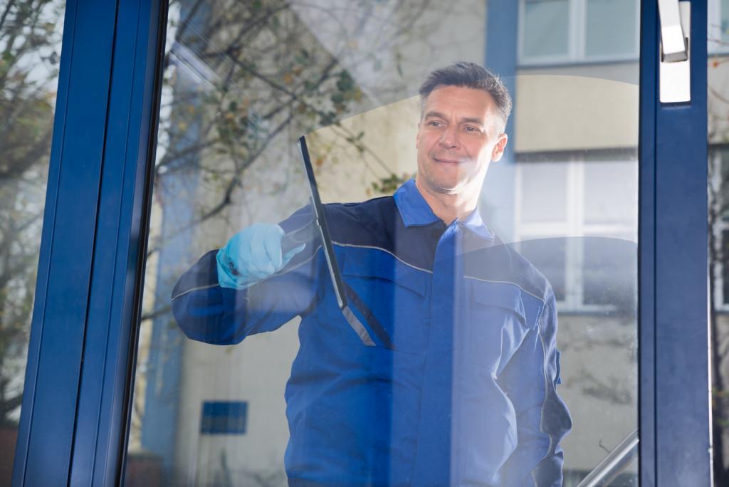 man cleaning window pane
